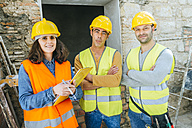 Woman with two construction workers on construction site - KIJF01243