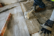 Close-up of construction worker placing flooring with a mallet - KIJF01258