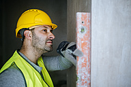 Construction worker using a water level on a wall - KIJF01261