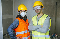 Portrait of woman with mask and man with safety glasses on a construction site - KIJF01264