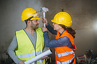 Playful man and woman fighting on a construction site - KIJF01267