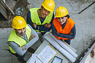 Portrait of smiling woman and two men in workwear with construction plan - KIJF01273