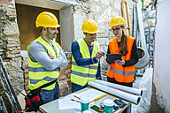 Woman and two construction workers with tablet on construction site - KIJF01276