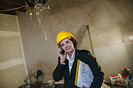 Woman wearing hard hat talking on phone on construction site - KIJF01282