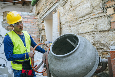 Construction worker working with a concrete mixer - KIJF01285