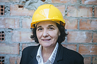 Portrait of confident woman wearing hard hat - KIJF01288