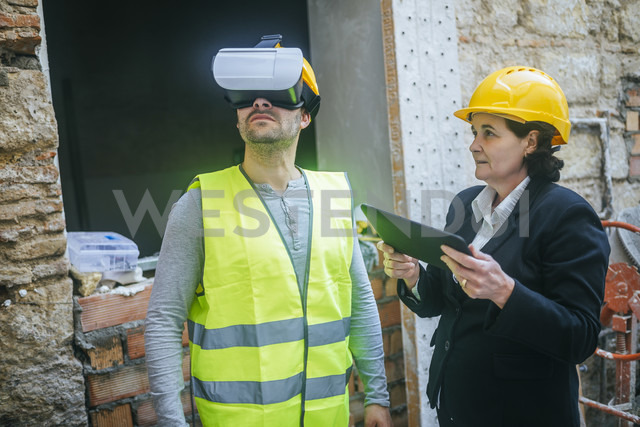 Woman with tablet and construction worker with VR glasses on construction site - KIJF01294 - Kiko Jimenez/Westend61