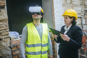 Woman with tablet and construction worker with VR glasses on construction site - KIJF01294