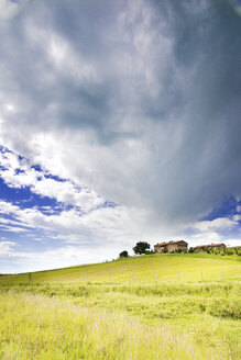 Italy, cloudy sky over houses on a hill - SIPF01425