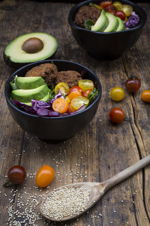Lunch bowls of leaf salad, red cabbage, avocado, tomatoes and quinoa fritters - LVF05896