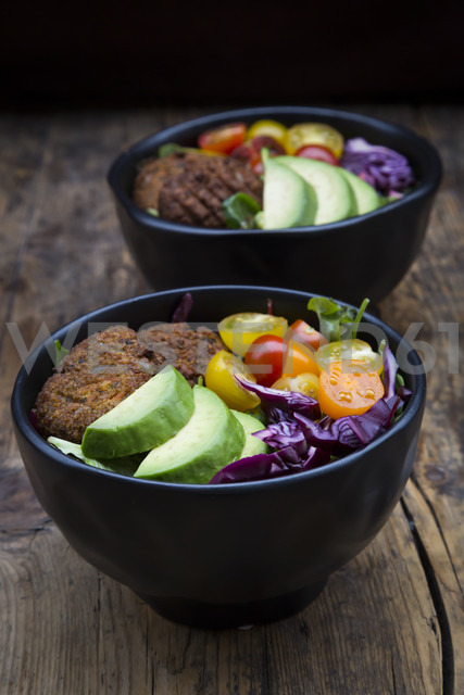 Lunch bowls of leaf salad, red cabbage, avocado, tomatoes and quinoa fritters - LVF05899