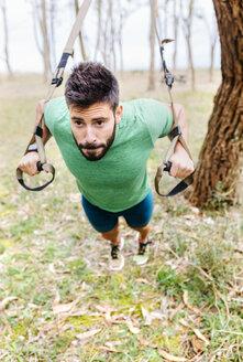 Man doing suspension traning outdoors - MGOF03003