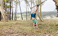 Man doing suspension traning outdoors - MGOF03006