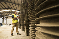 Worker in concrete factory inspecting metal tubes - JASF01553