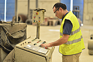 Worker in concrete factory pressing button on control panel - JASF01562