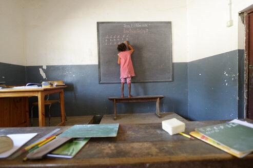 Madagascar, Fianarantsoa, Schoolgirl writing on blackboard - FLKF00744