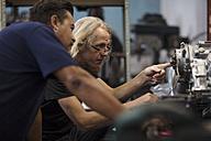 Two mechanics working on motorcycle engine in workshop - ZEF13010