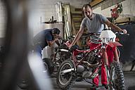Two mechanics in motorcycle workshop - ZEF13025