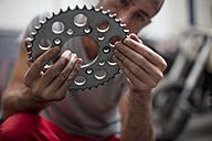 Mechanic in workshop holding a sprocket - ZEF13031