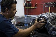 Mechanic working on motorcycle engine in workshop - ZEF13040