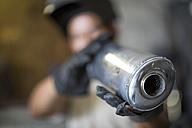 Mechanic in workshop holding motorcycle exhaust - ZEF13043