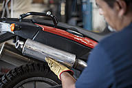 Mechanic working on motorcycle in workshop - ZEF13049