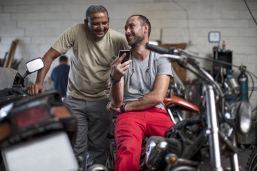 Two smiling mechanics in motorcycle workshop looking at cell phone - ZEF13052