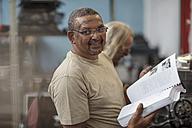 Portrait of smiling mechanic in workshop holding book - ZEF13058