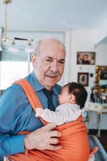 Portrait of great-grandfather carrying baby in a baby sling - GEMF01512
