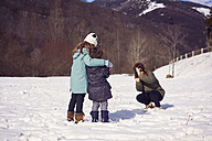 Mother taking picture of two children in winter landscape - XCF00139