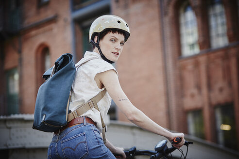 Portrait of young woman with cycling helmet and backpack on electric bicycle - RORF00642