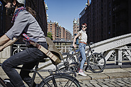Germany, Hamburg, woman with electric bicycle watching man passing by on bicycle - RORF00651