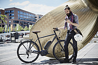 Man with electric bicycle looking at his cell phone - RORF00660