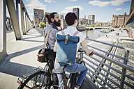 Germany, Hamburg, couple with electric bicycles on a bridge - RORF00663