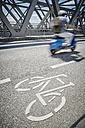 Germany, Hamburg, moped rider driving beside bicycle lane on a bridge - RORF00666