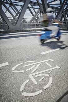 Germany, Hamburg, moped rider driving beside bicycle lane on a bridge - RORF00666