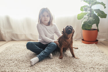 Little girl sitting with her dog on the carpet at home - RTBF00699
