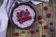 Bowl of overnight oats with blueberries and raspberries on wood - LVF05909
