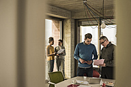 Business man showing document to colleague in office - UUF09987