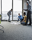 Businesspeople looking at documents on office floor - UUF10014