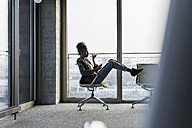 Businesswoman sitting on office chair using cell phone - UUF10032