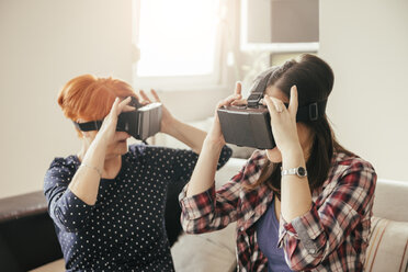 Adult daughter with mother at home wearing VR glasses - ZEDF00532