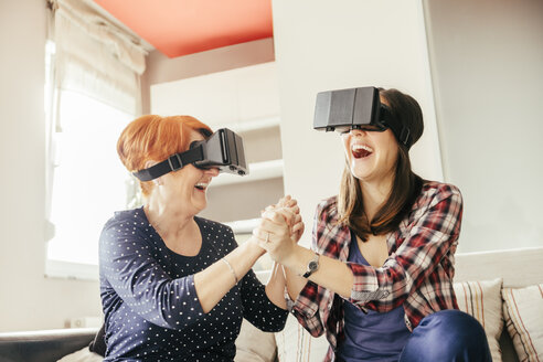 Excited adult daughter with mother at home wearing VR glasses - ZEDF00535