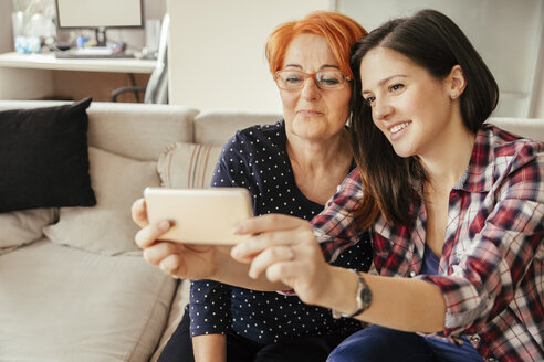 Adult daughter with mother at home taking a selfie - ZEDF00538