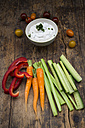 Bowl of herb yoghurt dip, cherry tomatoes and various vegetable sticks on wood - LVF05919