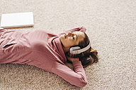 Woman lying on carpet wearing headphones - JOSF00633