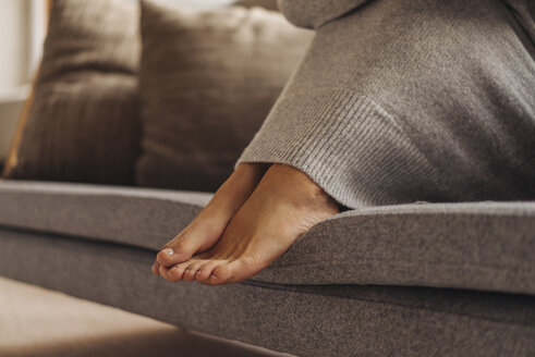 Close-up of woman's feet sitting on couch - JOSF00636