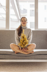 Woman with closed eyes sitting on couch holding small tree - JOSF00642