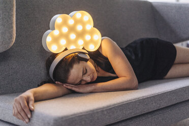 Woman lying on couch wearing headphones with illuminated cloud above her - JOSF00648