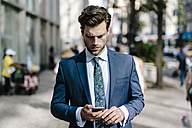 Handsome businessman walking in Manhattan, using mobile phone - GIOF02045